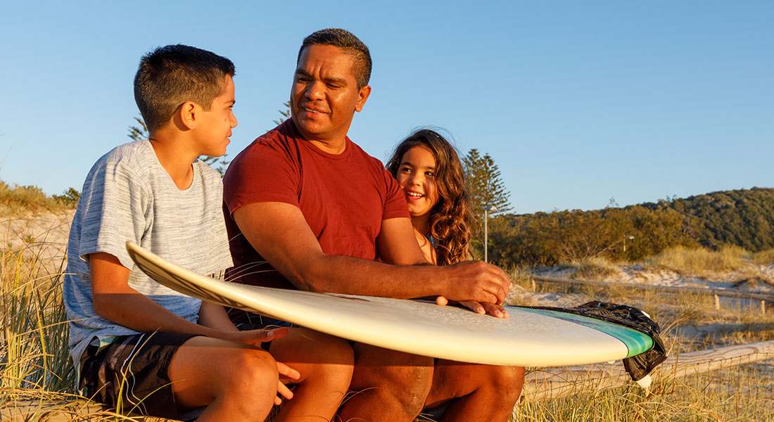 father-with-surfboard-and-kids